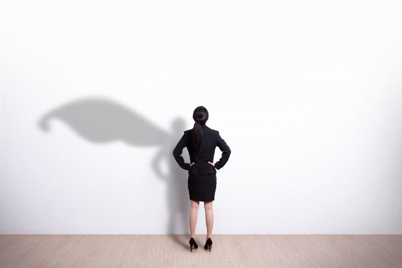 Superhelden-Geschaftsfrau-die-Wand-betrachtet