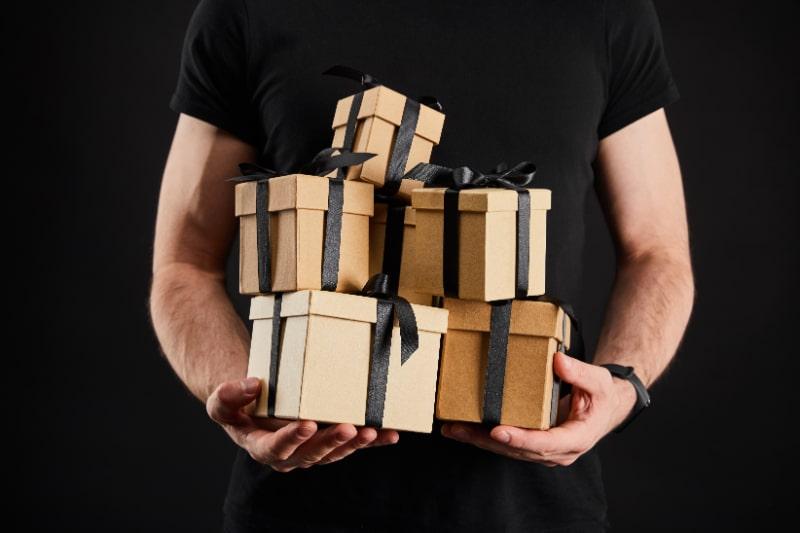 Teilansicht-des-Mannes-der-Geschenkboxen-des-Kartons-halt