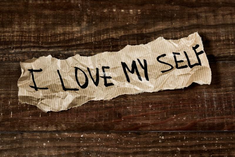 Text-ich-liebe-mich-selbst-geschrieben-in-ein-Stuck-Papier