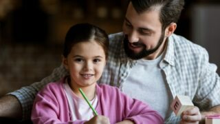 Vater mit Tochter sitzt am Tisch mit Würfelbuchstaben und Zeichnung