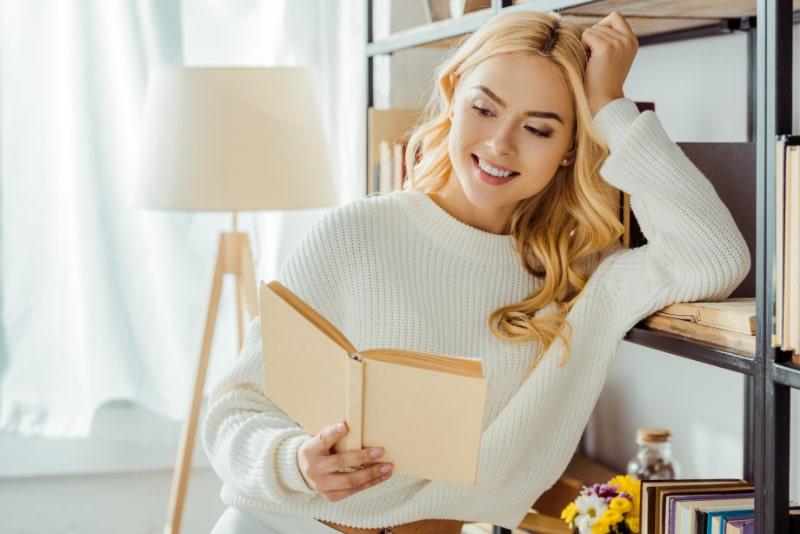 schone-lachelnde-Frau-die-Buch-nahe-Gestell-liest