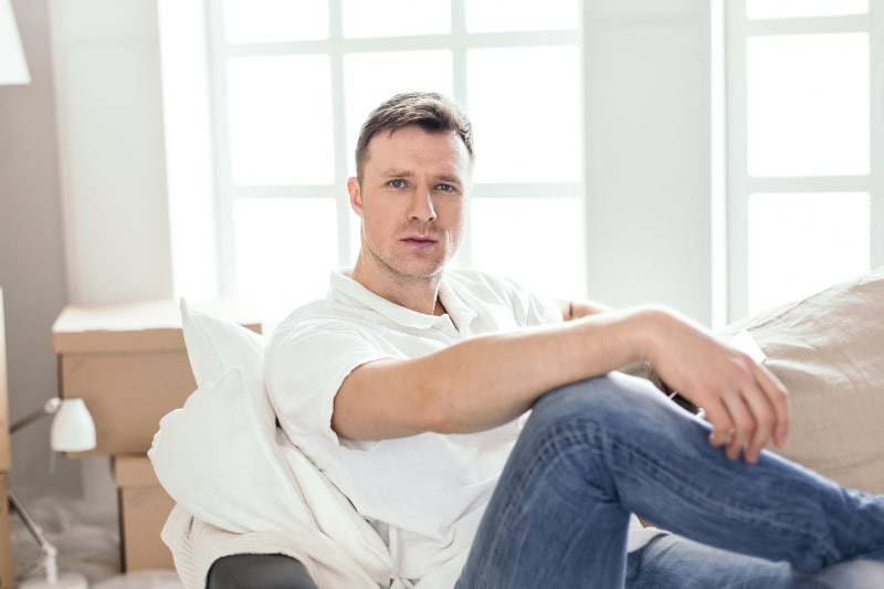 schoner-Mann-der-auf-einer-Couch-sitzt
