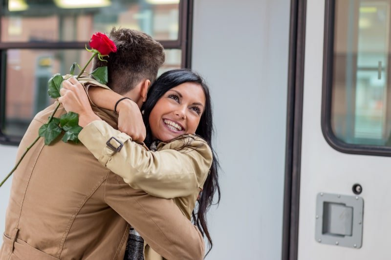 Anreise-mit-dem-Zug-Paar-umarmt-Frau-mit-roter-Rose