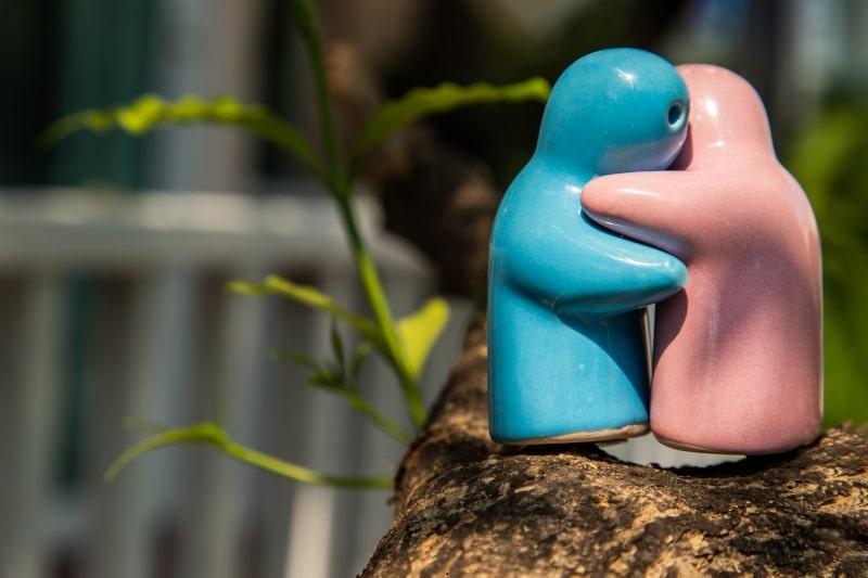 Blaue-und-rosa-Keramik-Paarpuppen-umarmen-sich-auf-dem-Baum.-Konzept-fur-Jubilaum-Hochzeit-und-ewiges-Liebeskonzept.