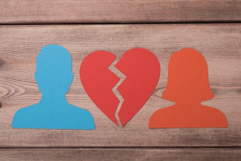 Die-Scherenschnitte-einer-mannlichen-und-weiblichen-Figur-mit-gebrochenem-Herzen-auf-einem-Holztisch