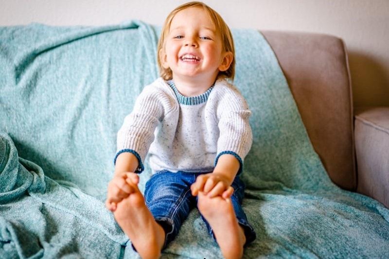 Ein-glucklicher-Junge-sitzt-auf-einer-grauen-Couch-mit-einer-ozeanblauen-Decke.-Er-tragt-blaue-Jeans-und-weisen-Pullover