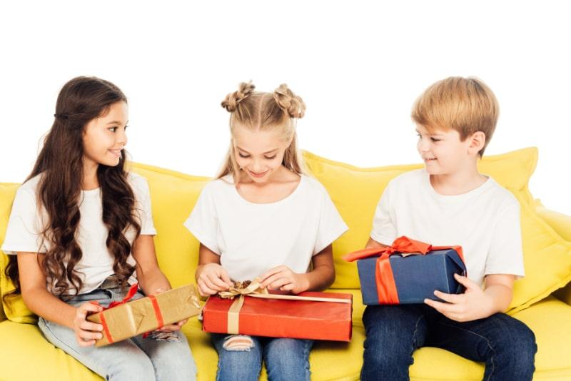 Entzuckende-Kinder-die-auf-einem-gelben-Sofa-sitzen-und-Geschenkboxen-offnen