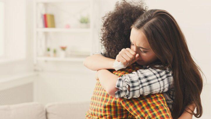 Frau umarmt ihren depressiven Freund zu Hause