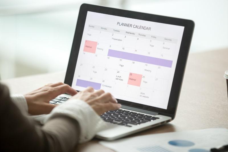 Geschaftsfrau-die-den-Tag-mit-digitaler-Planer-oder-Kalender-Softwareanwendung-auf-Laptop-Bildschirm-plant
