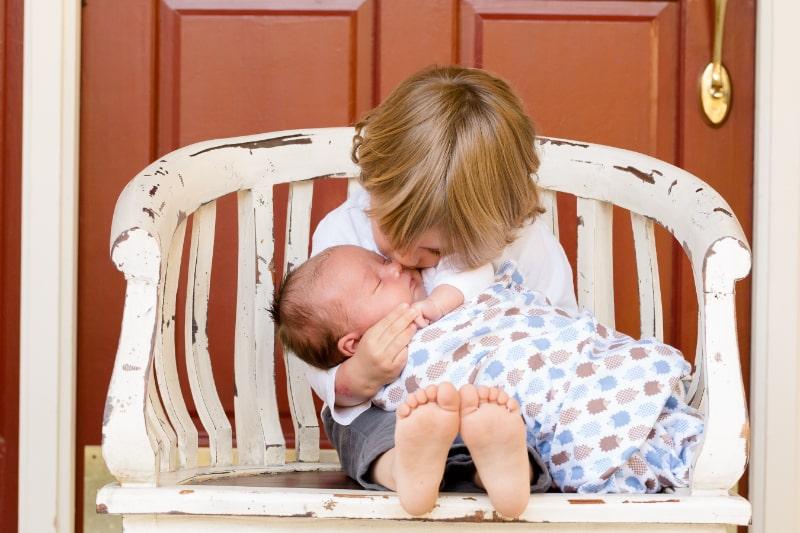 Geschwisterliebe-Kind-das-neugeborenes-Baby-kusst
