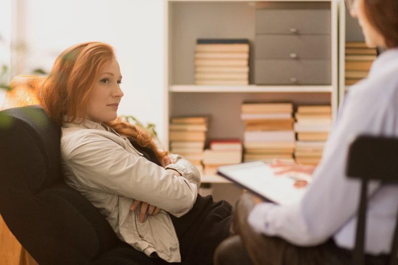 Gestresste-Frau-die-wahrend-der-Therapie-dem-personlichen-Lebenscoach-zuhort