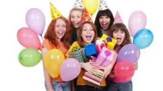 Glückliche Mädchen mit Kisten und Luftballons