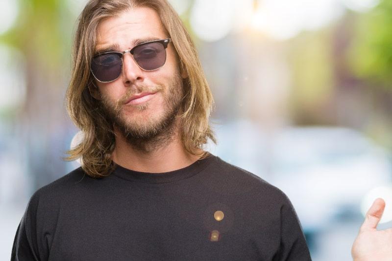 Junger-gutaussehender-Mann-mit-langen-Haaren-mit-Sonnenbrille