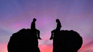 Junges Paar im Streit sitzt auf Felsen