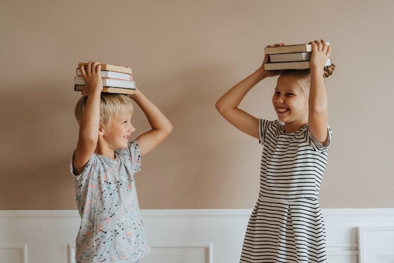 Kinder-die-Bucher-auf-dem-Kopf-halten