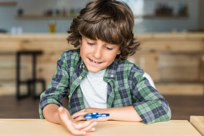 Lachelnder-Junge-mit-fidget-spinner
