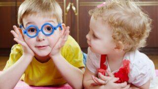 Lustiger Bruder in Spielzeugbrille mit Schwester auf dem Boden