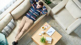 Mann entspannt sich auf der Couch im sonnendurchfluteten Büro