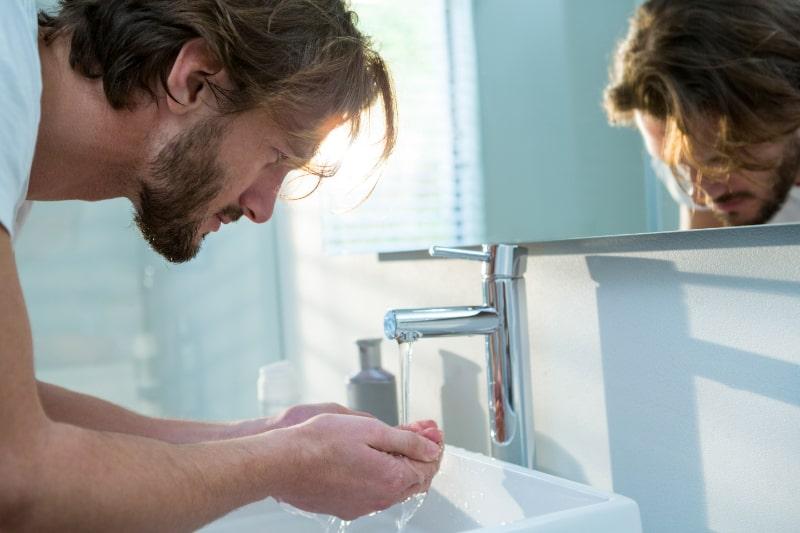 Mann-wascht-sein-Gesicht-mit-Wasser