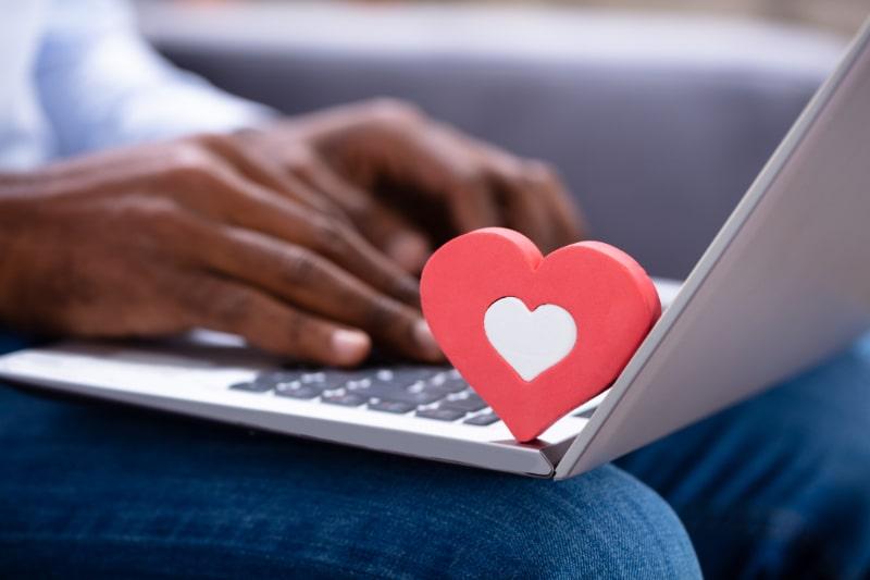 Nahaufnahme-der-roten-Herzform-auf-der-Tastatur-wahrend-die-Hand-des-Mannes-mit-Laptop