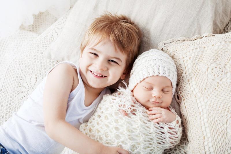 Neugeborenes-Baby-und-alterer-Bruder.-Junge-der-mit-neugeborenem-Bruder-liegt.