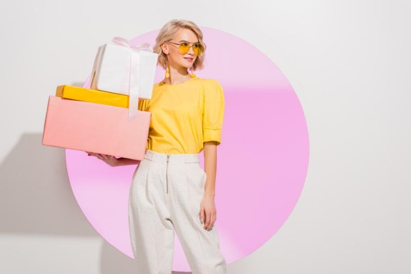 Schones-stilvolles-Madchen-das-Geschenkboxen-auf-Weis-mit-rosa-Kreis-halt