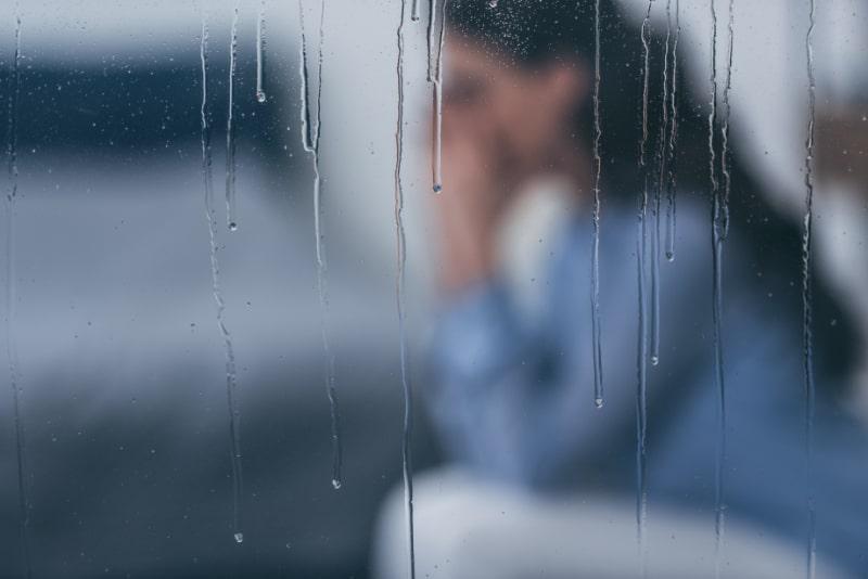 Selektiver-Fokus-von-Regentropfen-auf-Fenstern-mit-trauriger-Frau-die-im-Hintergrund-sitzt