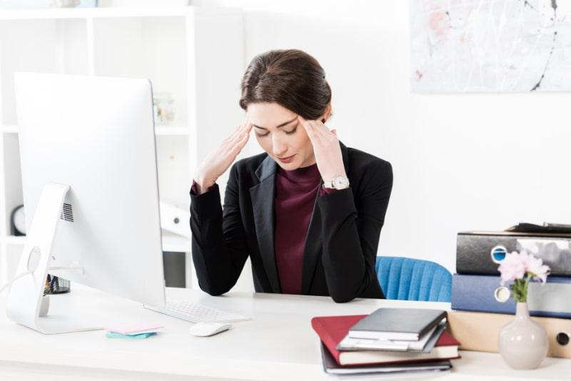 Traurige-erschopfte-Geschaftsfrau-die-Kopfschmerzen-hat-und-den-Kopf-beruhrt