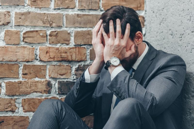 Trauriger-Mann-im-grauen-Anzug-der-das-Gesicht-mit-den-Handen-auf-braunem-strukturiertem-Hintergrund-im-Zimmer-sitzt-und-bedeckt-Konzept-der-Trauerstorung