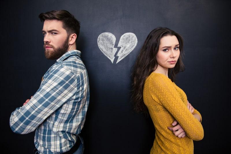Ungluckliches-Paar-das-uber-Tafelhintergrund-mit-gezeichnetem-gebrochenem-Herzen-steht