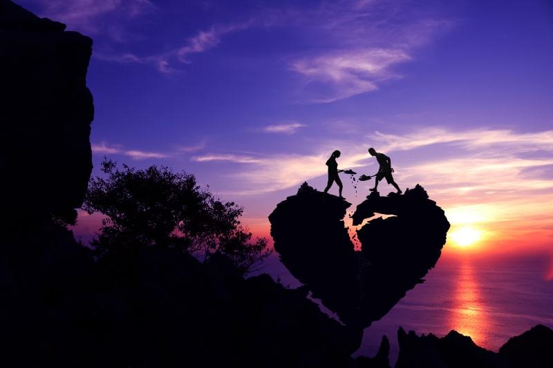 Valentinstag-Silhouette-Paar-das-hilft-Stein-fur-die-Reparatur-des-gebrochenen-Herzformfelsens-auf-dem-Berg-zu-schaufeln