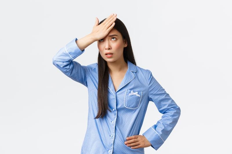 Verargertes-Madchen-im-blauen-Pyjama-rollte-die-Augen-belastigt-und-das-Gesicht-mit-der-Handflache-schlug-die-Stirn-mit-dem-Arm-vor-Reizung