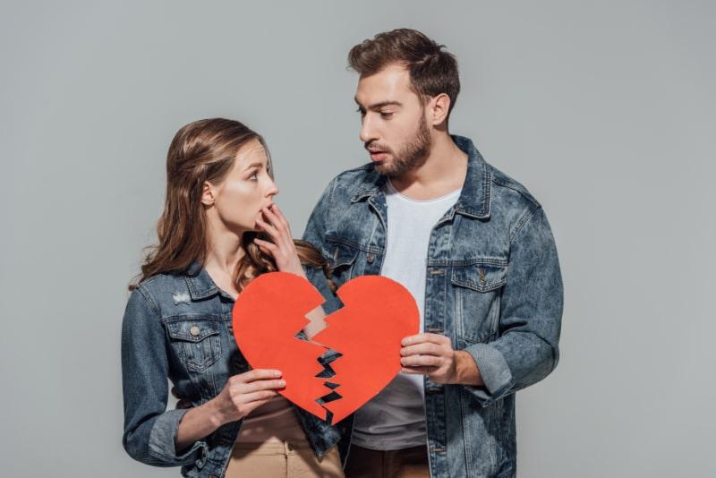 Verargertes-junges-Paar-das-Stucke-des-Symbols-des-gebrochenen-Herzens-halt