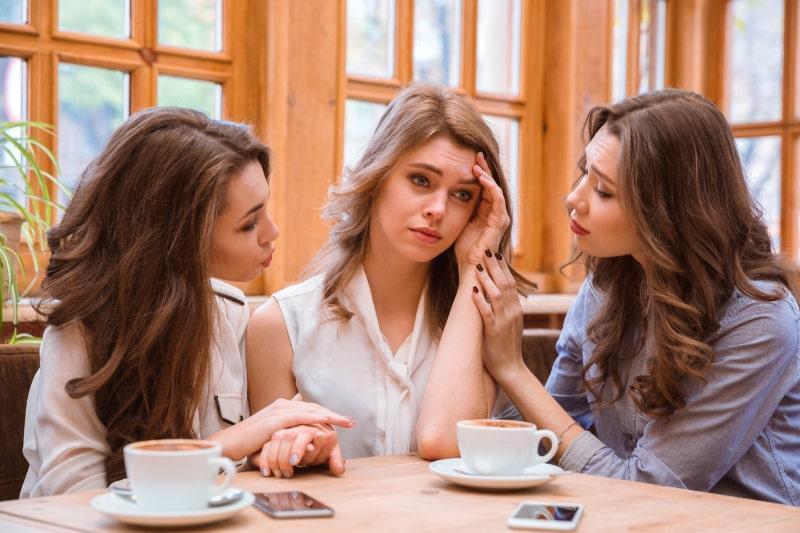 Zwei-Frauen-die-weinendes-Madchen-im-Cafe-trosten