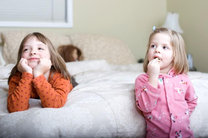 Zwei-suse-Schwestern-schauen-im-Schlafzimmer-ihrer-Eltern-fern
