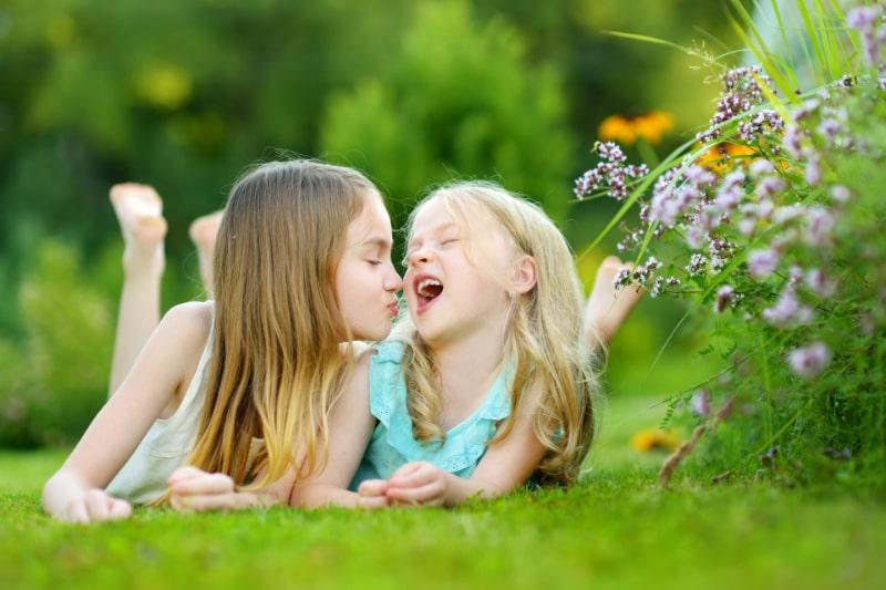 Zwei-suse-kleine-Schwestern-die-zusammen-Spas-auf-dem-Gras-an-einem-sonnigen-Tag-haben