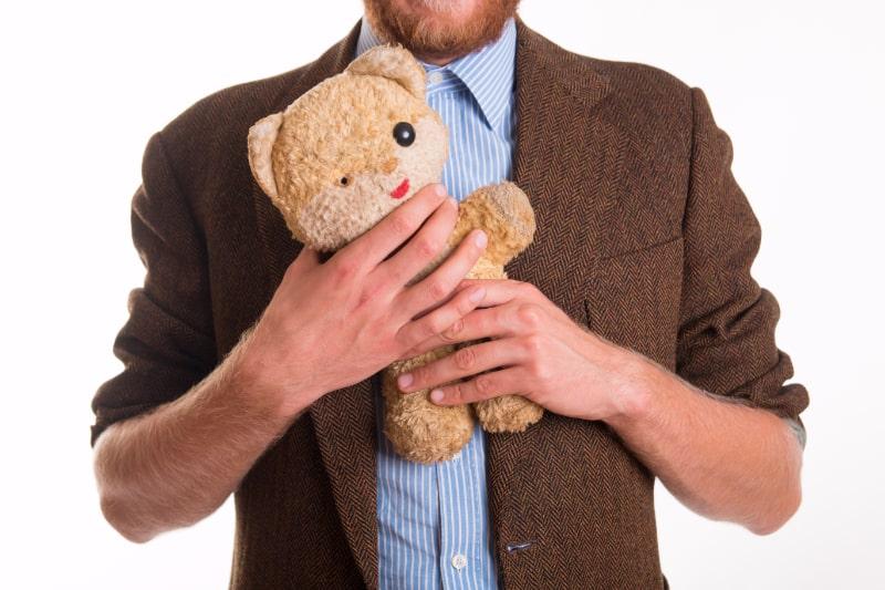 Alter-Teddybar-in-den-Armen-eines-Mannes