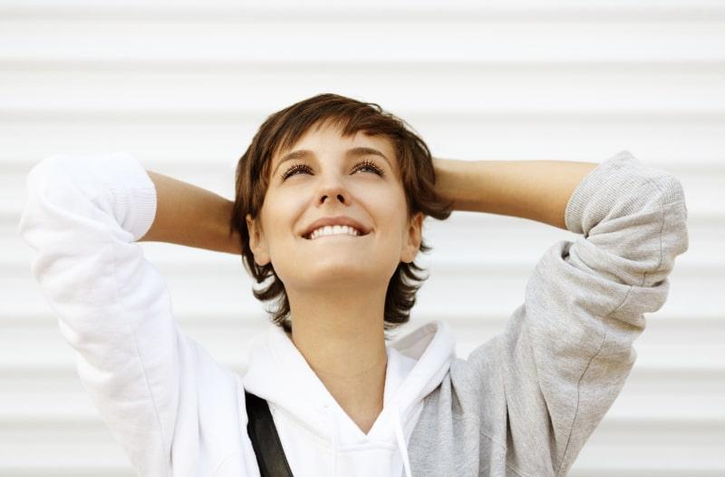 Denk-positiv-Frau-halt-sich-die-Hande-uber-den-Kopf-und-schaut-nach-oben