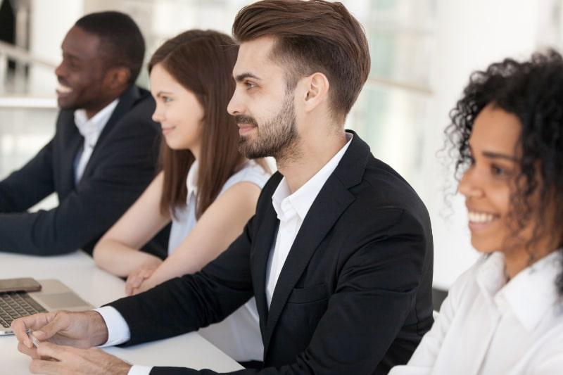 Diverse-Millennial-Recruiter-sitzen-am-Tisch-und-mogen-eine-Interviewkarte