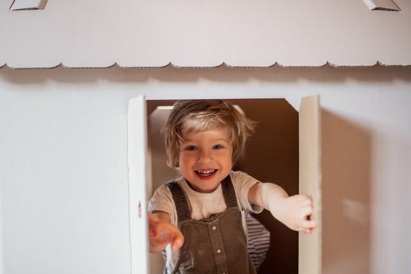 Ein-Kleinkindjunge-der-drinnen-mit-Papphaus-spielt