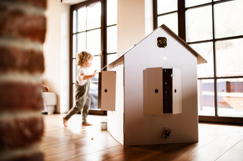 Ein-kleiner-Junge-der-mit-einem-Kartonpapierhaus-spielt