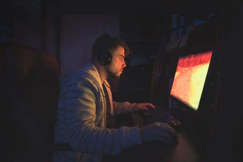 Ein-suser-mannlicher-Spieler-sitzt-in-einem-gemutlichen-Zimmer-hinter-einem-Computer-und-spielt