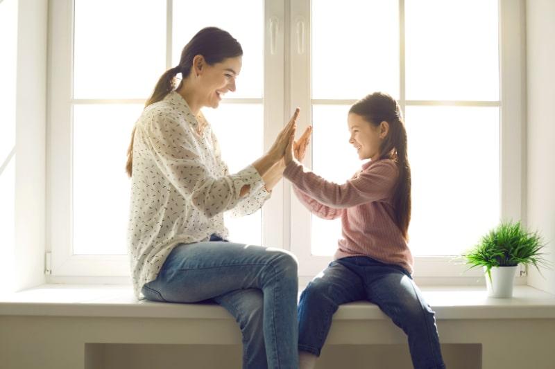 Frohliche-Mutter-und-Tochter-spielen-lustige-Spiele-mit-der-kleinen-Tochter-die-in-die-Hande-klatscht.