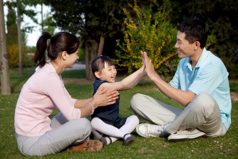 Gluckliche-Familie-die-im-Park-Klatschspiele-spielt