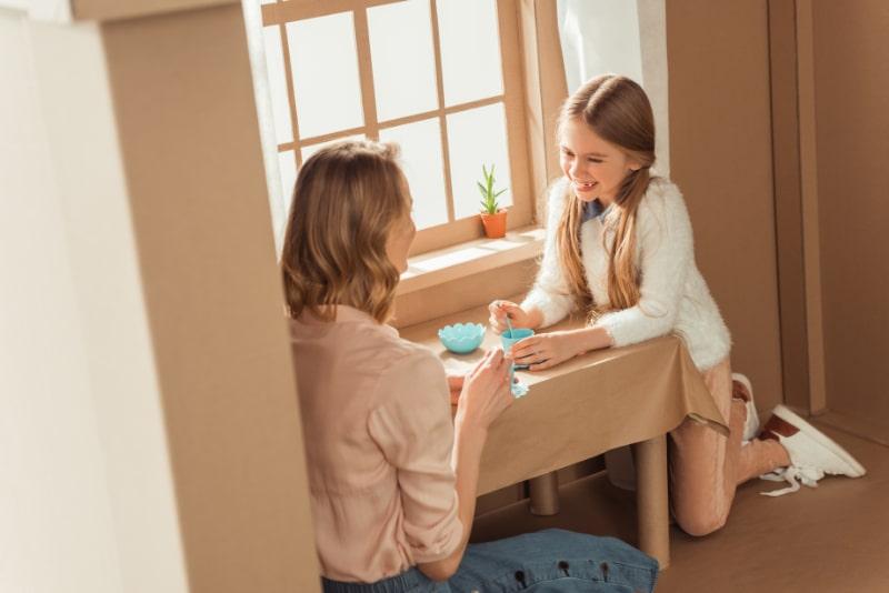 Gluckliche-Mutter-und-Tochter-mit-Teeparty-im-Papphaus