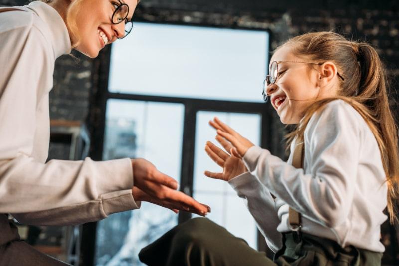 Gluckliche-junge-Mutter-und-Tochter-die-Pattycake-Klatschspiel-spielen