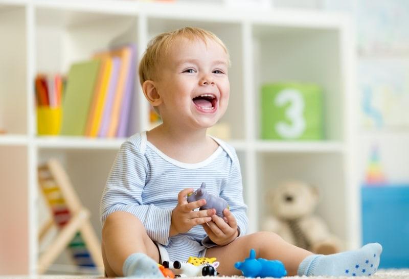 Glucklicher-kleiner-Junge.-Lachelndes-Kind-spielt-Tierspielzeug-zu-Hause-oder-im-Kindergarten.