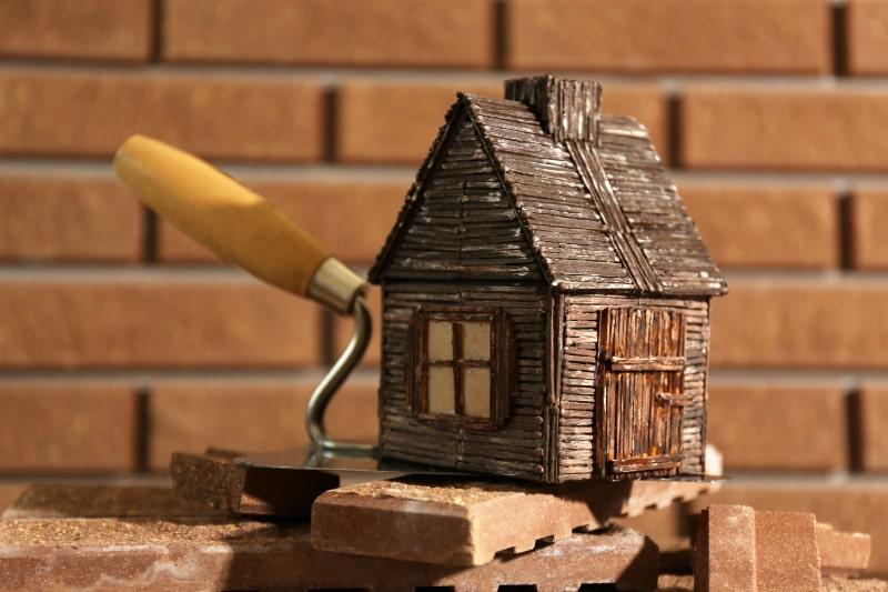 Holzspielzeughaus-auf-Kelle-und-Fliesen-auf-Backsteinmauer-brick