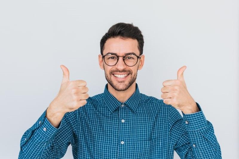Hubscher-Mann-mit-Lacheln-tragt-runde-Brille-blaues-Hemd-in-die-Kamera-schaut-und-mit-beiden-Handen-Daumen-nach-oben-zeigt.-Korpersprache