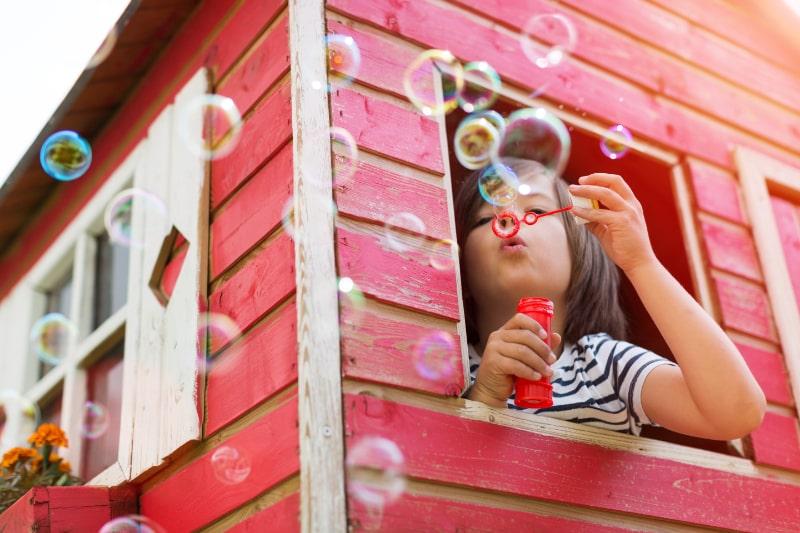 Junge-blast-Seifenblasen-in-einem-Holzspielhaus